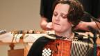 Eine junge Frau spielt Akkordeon.