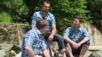 Drei junge Männer mit karierten Hemden sitzen an einem Fluss.