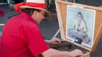 Ein Mann mit Strohhut und rotem Hemd sitzt an einem Hackbrett.
