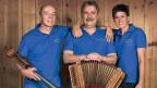 Zwei Männer und eine Frau in blauen Polo-Shirts und mit Instrumenten.