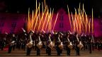 Militärmusikformation in einem grossen Kasernenhof bei Nacht.