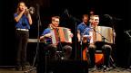 Eine junge Volksmusikformation auf einer grossen Bühne.