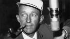 Ein Mann mit weisser Mütze und Tabakpfeife vor einem Mikrofon.