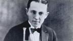 Schwarzweiss Foto eines jungen Mannes mit Blasinstrument.