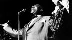 Louis Armstrong steht singend am Mikrophon und hält seine Trompete in der Hand.