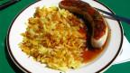 Ein Teller mit Rösti und Bratwurst.