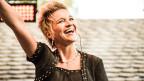 Eine lachende Sängerin mit kurzen blonden Haaren auf der Bühne.