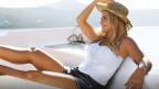Frau liegt auf Boot und geniesst die Sonne.