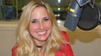 Eine blondhaarige Frau vor einem Mikrofon in einem Radiostudio.