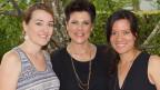 Gruppenbild mit drei lachenden Frauen in der freien Natur.
