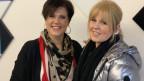 Zwei Frauen vor Wand mit bunten Kacheln.