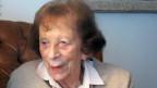 Eine alte Frau in einem braunen Ledersessel.