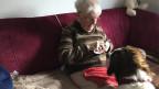 Eine ältere Frau sitzt auf einem grossen Sofa und füttert eine Bernhardiner-Hündin.