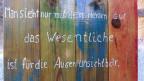 Ein mit weisser Farbe geschriebener Spruch auf verschiedenen farbigen Brettern.