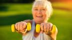 Eine ältere blondhaarige Frau mit zwei kleinen gelben Hanteln.