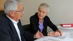 Ein Mann und eine Frau sitzen an einem Tisch, auf dem verschiedene Formulare liegen.