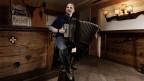 Ein Akkordeonspieler sitzt auf einem Barhocker.