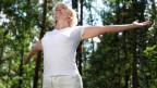 Frau streckt sich freudig in der Natur.