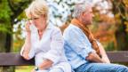 Frau und Mann sitzen mit dem Rücken gegeneinander auf einer Parkbank. Die Frau weint und hält ein Taschentuch in der Hand.