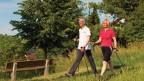 Frau und Mann walken über eine Wiese.