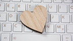 Ein Herz aus Holz auf einer Computer-Tastatur.