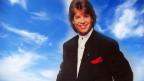 Ein Mann mit dunklen Haaren vor einem «himmlischen» Hintergrund.