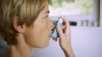Frau inhaliert mit Asthmagerät.