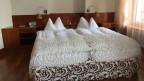 Bett mit Spitzendeckenbezug und Bildern aus Stoff an der Wand.