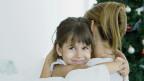 Ein kleines Mädchen umarmt seine Mutter.