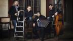 vier Männer auf Stühlen mit Instrumenten.