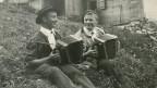 Hans Schmid und Lorenz Giovanelli sitzen zusammen auf einer Wiesen und spielen Handorgel.
