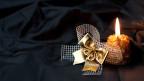Eine brennende Weihnachtskerze auf schwarzem Stoff.