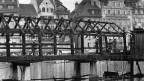 Abgebrannte Kapellbrücke mit Feuerwehrleuten.