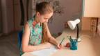 Ein Mädchen schreibt mit der linken Hand.