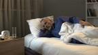 Ein Mann liegt wach in einem Bett.