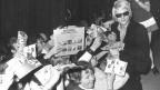 Ein blonder Sänger mit Sonnenbrille verteilt Autogramme.