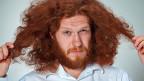 Ein Mann mit langen, dichten, roten Haaren.