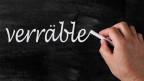 Jemand schreibt mit weisser Kreide das Wort «verräble» auf eine Wandtafel.