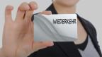 Konturen einer Frau, die eine Visitenkarte mit dem Namen Wiederkehr zeigt.