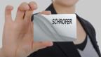 Frau hält Zettel mit Familiennamen in die Kamera.