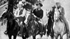 Vier Farmer auf Pferden.