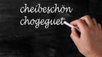 Ein Mann schreibt mit Kreide die Wörter «cheibeschön» und «chogeguet» auf eine Wandtafel.