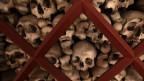 Knochen aufgeschichtet in einem Beinhaus.