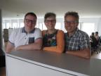 Drei Menschen lehnen an Tisch und posieren für Foto.
