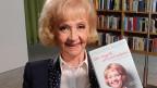 Eine Frau mit blonden Haaren hält ein Buch in der Hand.