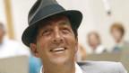 Ein lachender Mann mit Hut.