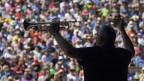 Ein auf der Bühne Mann hält eine Trompete in die Luft.