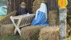 Maria- und Josef-Figuren beim Jesuskind zwischen Strohballen.