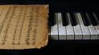 Ein vergilbtes Notenblatt auf Klaviertasten.