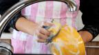 Eine Frau spült Geschirr.